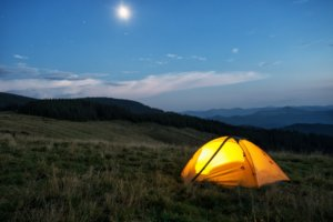 Illuminated orange tent in mountains at dusk