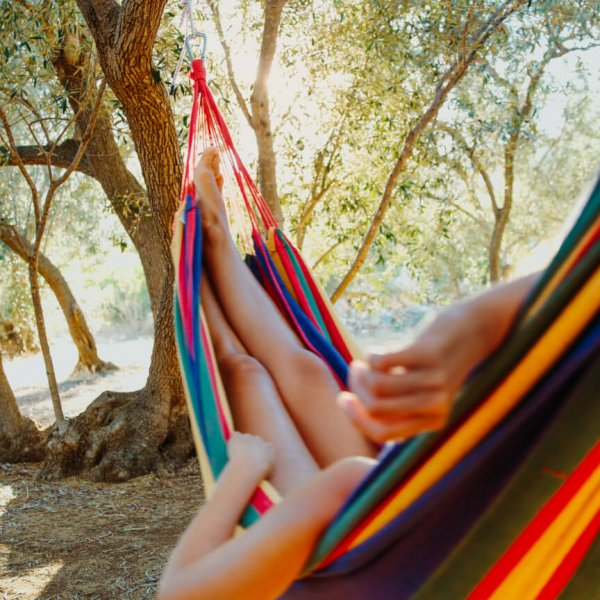 Close up of tourist lying in hammock among olive trees with bicycles in background,Croatia