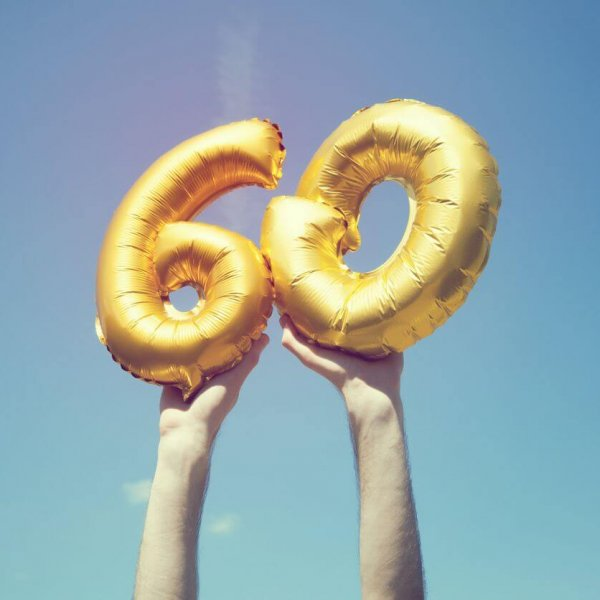 A gold foil number 60 balloon is held high in the air by caucasian male hand.  The image has been taken outdoors on a bright sunny day, the sky is blue with some clouds. A vintage style effects has been added to the image.