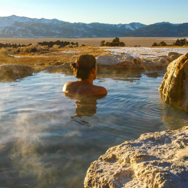 Woman enjoys view of Sierra Nevada Mountains while soaking in hot spring.